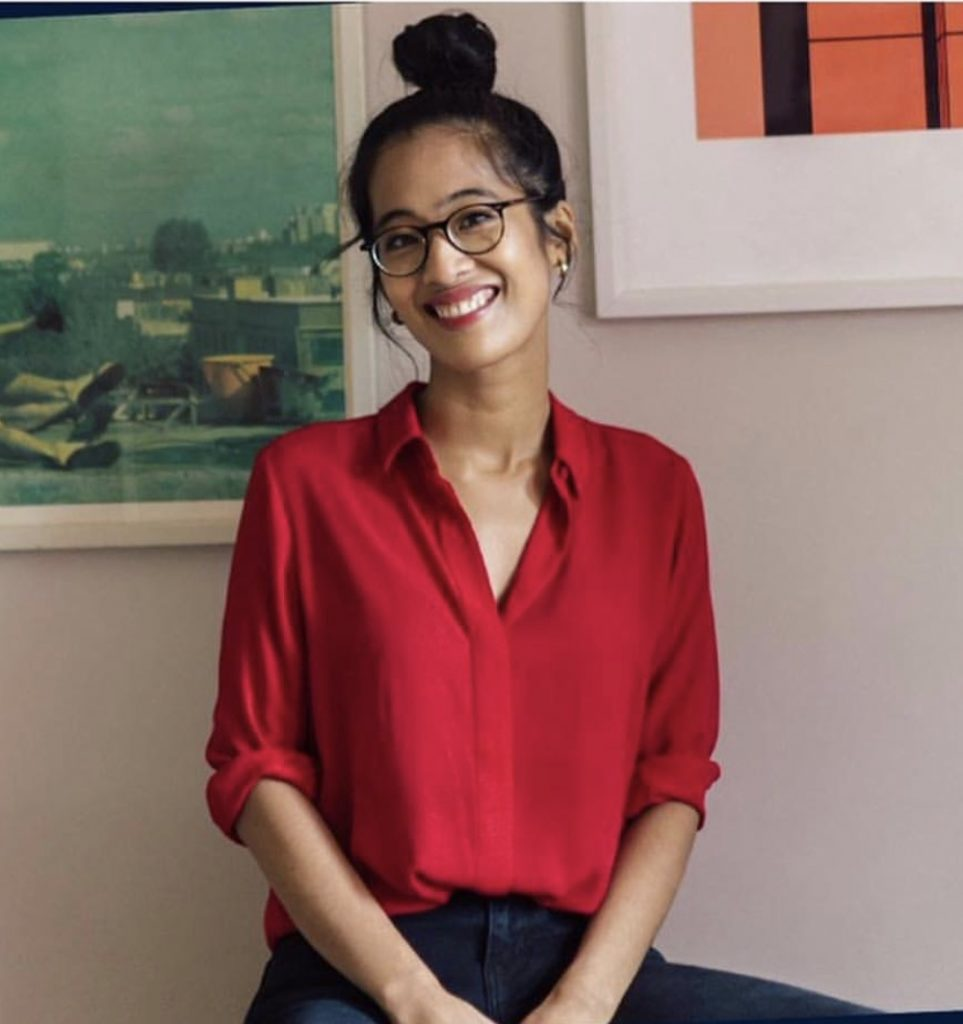 Woman in red blouse with hair in high bun. She wears glasses and smiles at the camera.