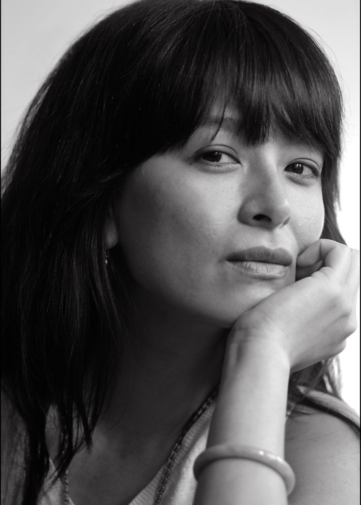 black and white photo of woman with dark hair and bangs. She rests her head on her hand and looks into the camera with her mouth slightly smiling